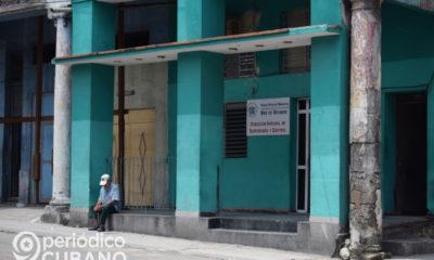 Hombre sentado en frente a una estación de policía en 10 de Octubre, La Habana