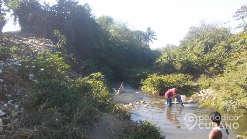 Guantanameros sin servicio de agua potable se abastecen de un río contaminado